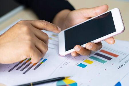 Photo for Accounting press mobile phone with calculator and chart graph for working project in modern office. - Royalty Free Image
