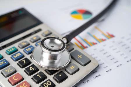 Foto de Stethoscope with calculator on chart graph paper, finance, account, statistic, analytic economy Business concept. - Imagen libre de derechos
