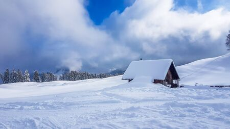 Photo pour A wooden cottage next to the ski slopes in Heiligenblut, Austria. Cottage covered with snow. Perfectly groomed ski slope. Some pine trees. Blue sky. Winder wonderland. Off road skiing. - image libre de droit
