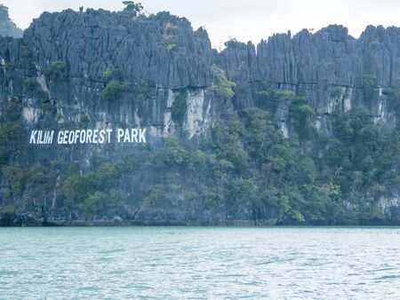 Photo pour The Kilim Geoforset Park sign, seen from a boat. The sigh is situated on a mountain, rocky surface. Calm water washes the mountains. Overcast. Some smaller bushed growing on a steep rock. - image libre de droit
