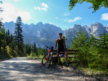 Photo pour A man in biking outfit standing next to orange mountain bike next to a gravelled road in the mountains with the view on high Alps in the region of Gosau, Austria. Stony and barren mountain chains. - image libre de droit