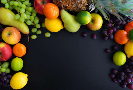 Foto de different fresh healthy fruits on black background - Imagen libre de derechos