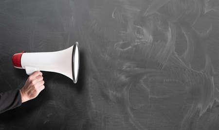 Foto de hand holding red and white megaphone against chalkboard template - Imagen libre de derechos