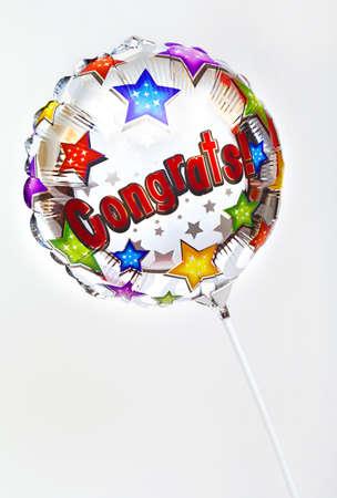 A 'Congratulations' balloon over a plain background.