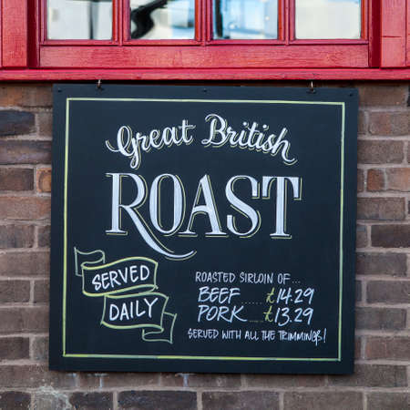 A sign on a trdaitional English Public House advertising their traditional Sunday Roast Dinners.