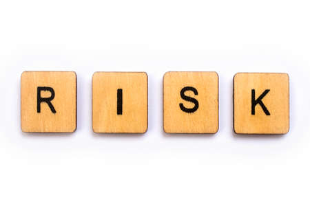 The word RISK, spelt with wooden letter tiles.
