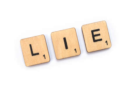LONDON, UK - JULY 5TH 2018: The word LIE, spelt with wooden letter Scrabble tiles, on 5th July 2018.