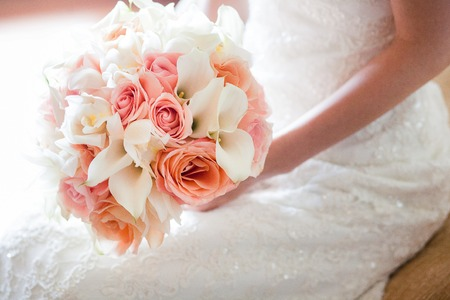 Foto de Bride with beautiful orange and pink wedding bouquet of flowers consisting of white mini calla lilies,roses, and white orchid. - Imagen libre de derechos