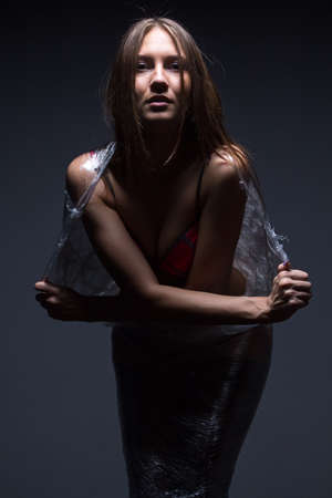 Portrait of young wraped girl on black background