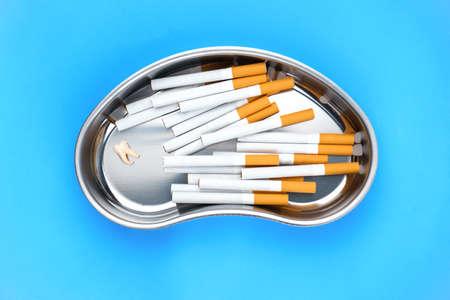 Photo pour Image of kidney-shaped bowl with cigarettes on blue background - image libre de droit