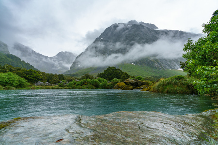 turquoise water of a river in the mountains in the rain, gertrude valley lookout, southland, new zealand