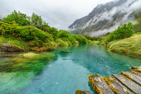 wooden bridge over turquoise water of a river in the mountains in the rain, gertrude valley lookout, southland, new zealand