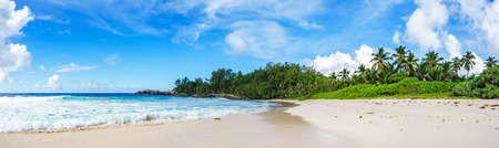 Photo pour Beautiful and wild lonely tropical beach with rough granite rocks, white sand, palm trees in a jungle and turquoise water of the indian ocean at police bay on the seychelles - image libre de droit