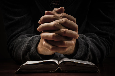 Photo pour Praying man hand and bible on desk. - image libre de droit
