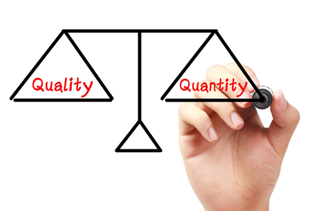 Hand with marker is drawing Quality and quantity balance scale on the transparent white board.