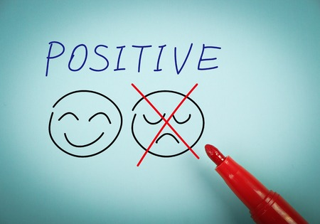 Positive thinking concept is on blue paper with a red marker aside.