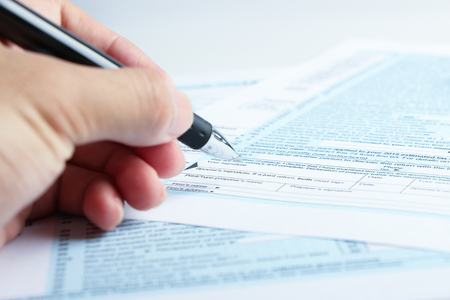 Photo pour A person is completing the tax form with a pen. - image libre de droit