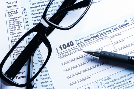 Tax form business financial concept with a pair of black glasses and a pen aside.