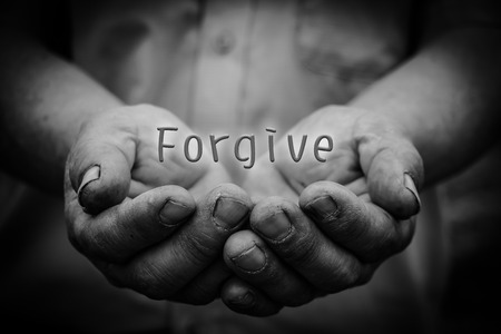 Photo for Forgive text is in the holding hands with dark corners. - Royalty Free Image