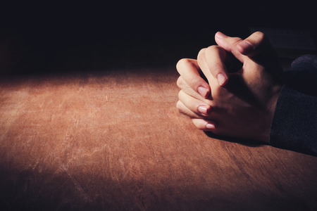 Photo for Praying hands of young man on a wooden desk background. - Royalty Free Image