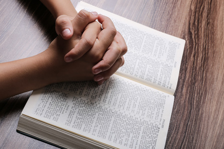 Photo for Praying hands with opened holy bible on the wooden desk. - Royalty Free Image