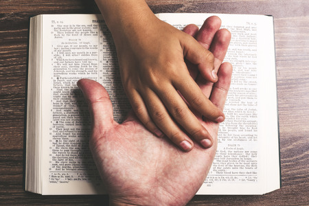 Photo for The hands of child and man on the holy bible. - Royalty Free Image