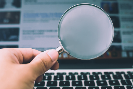 Photo pour Magnifying glass with the laptop background. - image libre de droit