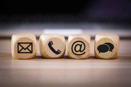 Photo for Contact Methods. Close-up of a phone, email, chat and post icons wooden block. - Royalty Free Image