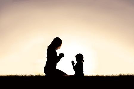 Photo pour A silhouette of a Christian mother teaching her young child to pray as they sit peacefully outside, against the sunset in the sky. - image libre de droit