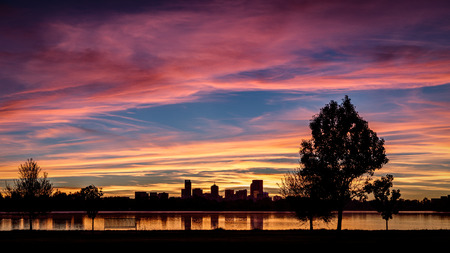 Downtown Denver skyline at sunrise with lake reflection