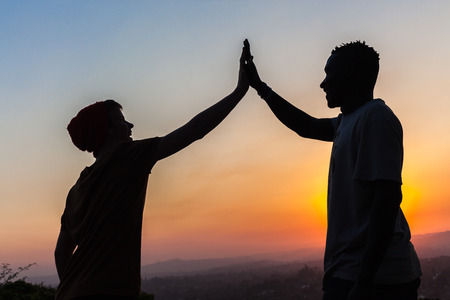 Friends high five hands against sunset dusk sky with body outlines silhouetted