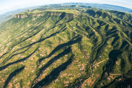 Photo pour Air birds eye view flying thousand valley hills with habitat homes over the colorful landscape - image libre de droit