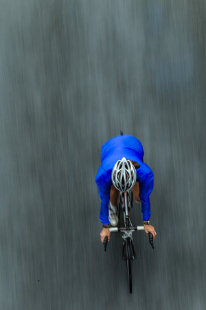 Photo pour Cycling race woman rider birds eye view overlooking in color speed blur in race - image libre de droit