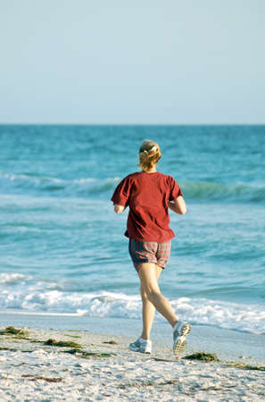 Young woman jogging along the beach.