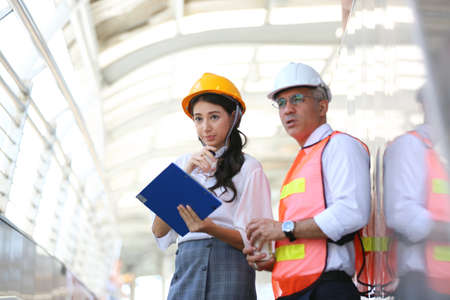 Photo pour Female industrial engineer wearing a white helmet while standing in a construction site with businessman talking on working plan, Engineer and architects at construction site concept - image libre de droit