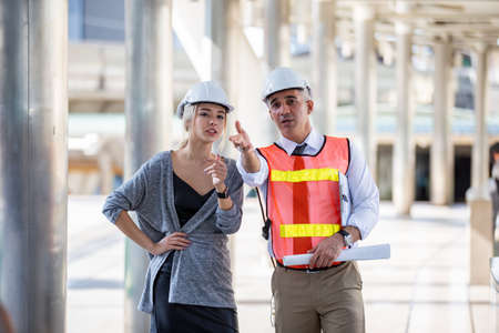 Photo for Female industrial engineer wearing a white helmet while standing in a construction site with businessman talking on working plan, Engineer and architects at construction site concept - Royalty Free Image