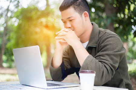 Young business man working on laptop computer while sitting in vintage cafe bar.
