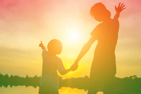 Photo for Mother encouraged her son outdoors at sunset, silhouette concept - Royalty Free Image