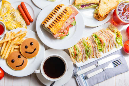 Photo pour Breakfast on the dining table, There are sandwiches, submarine sandwiches, burgers, pancakes, eggs, vegetables and coffee  - image libre de droit
