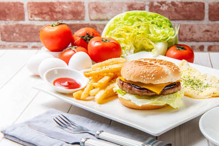 Photo pour Breakfast with beef cheese burger, eggs, vegetables and drinks on the table - image libre de droit