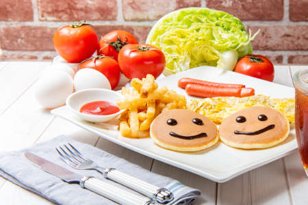 Photo pour Breakfast with pancakes, french fries, German sausages, eggs, vegetables and drinks is on the table  - image libre de droit