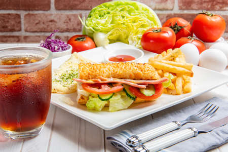 Photo pour  Breakfast with bacon submarine sandwiches, eggs, vegetables and drinks on the table - image libre de droit