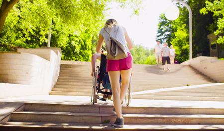 Photo pour Disable man in a wheelchair is moving down the steps - image libre de droit
