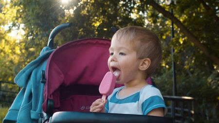 Photo for Happy small boy sitting in a stroller and eating ice cream - Royalty Free Image