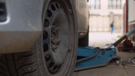 Photo pour Mechanic in a vehicle workshop lifting a car on a jack. Car wheel replacement in a car service. Close up. - image libre de droit