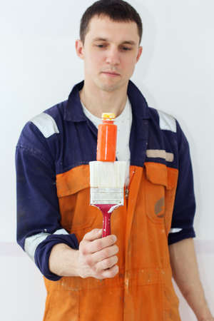 Guy painter with paint brush and orange color tube