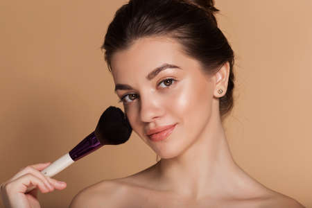 Photo for Closeup portrait of beautiful happy young girl with perfect skin is holding makeup brush in hand. Isolated on beige. Beauty and cosmetics concept. - Royalty Free Image