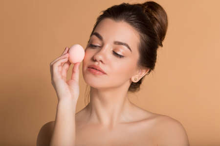 Photo pour Closeup portrait of young beautiful woman is holding beauty blender for applying makeup foundation . Skin care and beauty concept. - image libre de droit