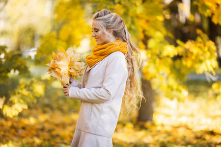 Photo pour Pretty blonde teen girl is walking in autumn park with yellow leaves - image libre de droit