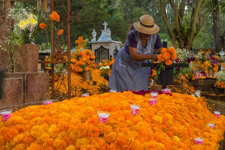Photo pour The lady adorns the tomb with flowers of cempasuchil the day of the dead. - image libre de droit
